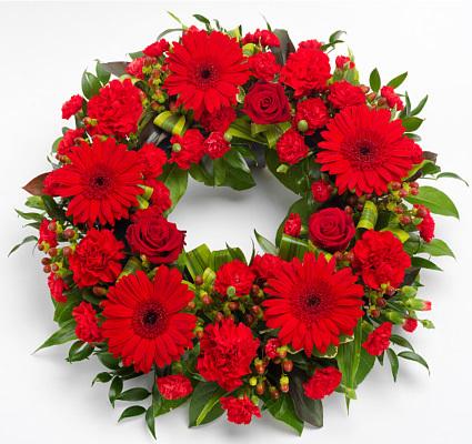 Ανθοσύνθεση με κόκκινα τριαντάφυλλα, ζέρμπερες και λουλούδια εποχής